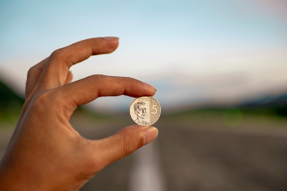 person with a coin in hand depicting budgeting and forecasting as two sides of the same coin