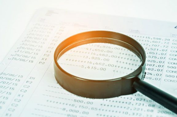 A conceptual image showing a financial document and magnifier on a desk