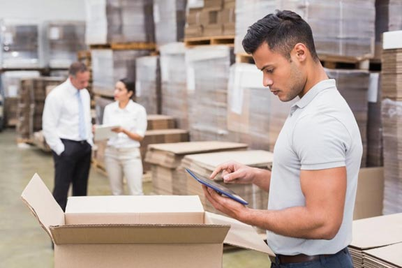 A warehouse manager checking inventory via iPad