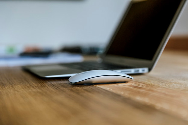 A laptop and mouse on a wooden work desk
