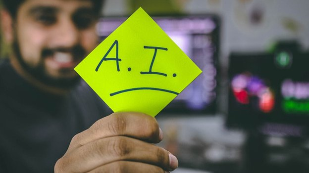 A man holding a paper with AI written on it
