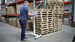 A warehouse manager using QuickBooks on a tablet